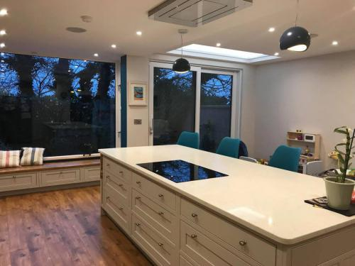 White kitchen island, picture window and blue counter stool